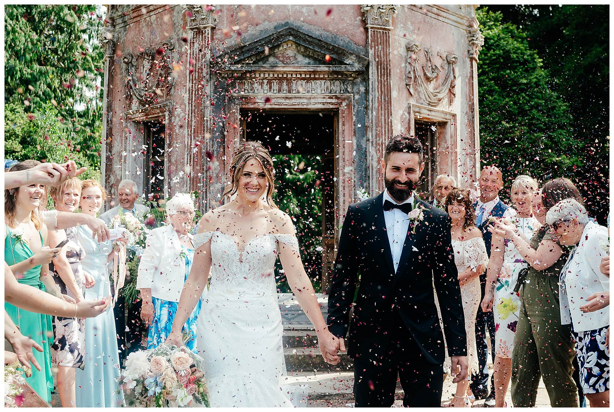 colourful Larmer tree wedding photographer - a couple walking down the aisle